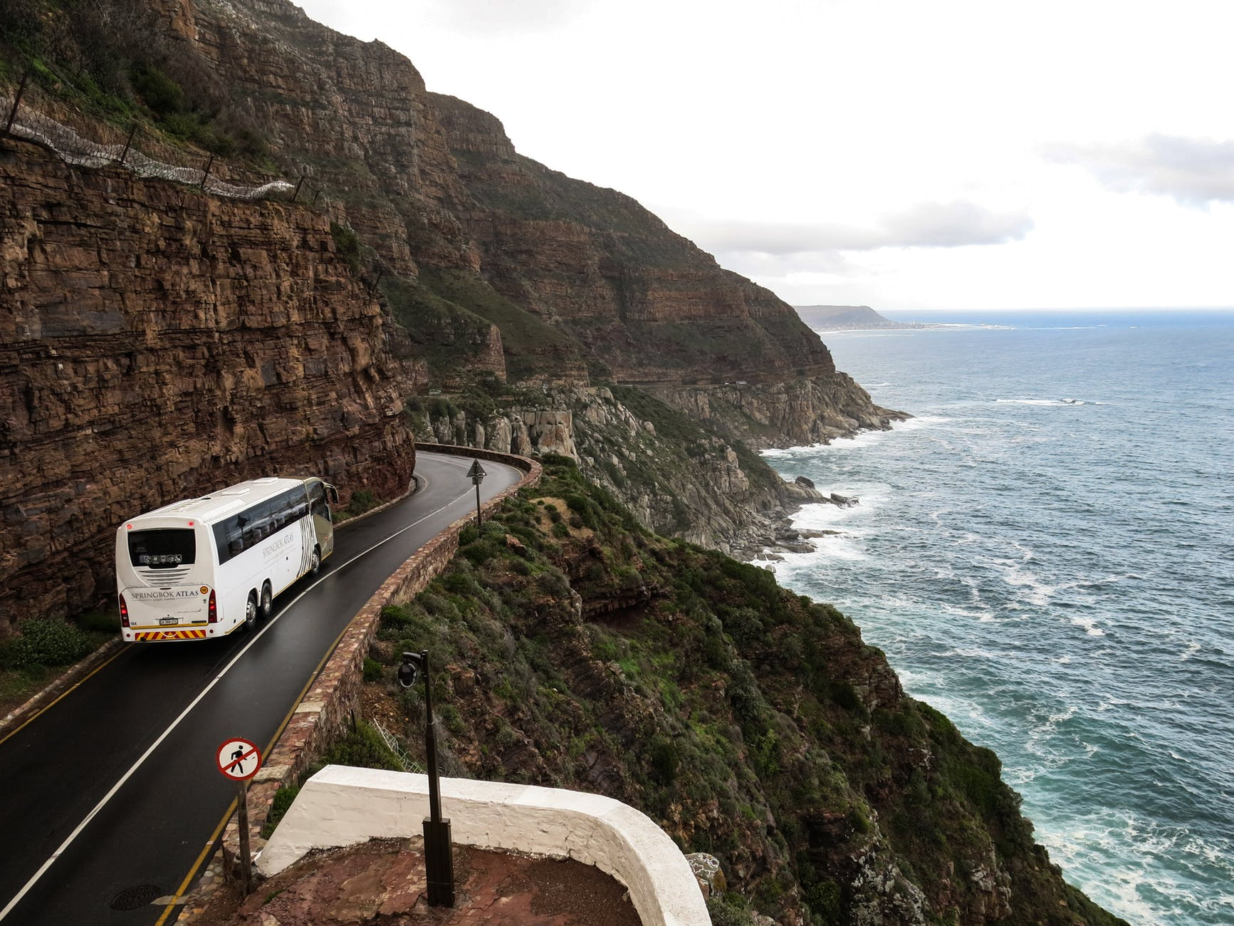 white bus on road near cliff
